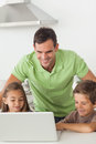Man and his children using a laptop together in the kitchen Stock Photography