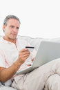 Man on his couch using laptop for shopping online at home in living room Royalty Free Stock Photo