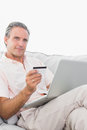 Man on his couch using laptop for shopping online smiling at cam camera home in living room Stock Photos