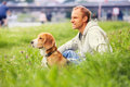 Man with his dog sitting in green grass Royalty Free Stock Photo