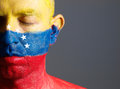 Man and his face painted with the flag of venezuela and closed e has eyes photographic composition leaves only half Stock Image