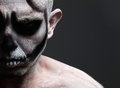 Man with his face painted with a skull and isolated on black background Royalty Free Stock Image