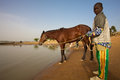 A man and his horse mali djenne january unidentified young close at the niger river on the way to djenné with blue sky Royalty Free Stock Photography