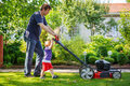 Man and his little son having fun with lawn mower in garden summer Royalty Free Stock Photos
