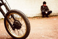 Man and his motorcycle sitting against a wall by Royalty Free Stock Photos