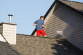 Man on his roof power washing the vinyl siding Royalty Free Stock Photo