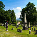 Man in historic cemetery a looks at the of the first church of old bennington vermont whose gravestones are from the revolutionary Royalty Free Stock Image