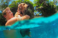 Man hold in hands golden labrador retriever in swimming pool