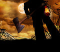 Man holding ax and lantern a dark with an a walks through bramble with the full moon in a golden cloudy sky Stock Photo
