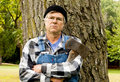 Man holding an axe leaning against a tree Royalty Free Stock Photography