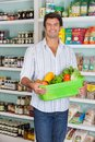 Man holding basket of vegetables in supermarket portrait happy mid adult Stock Images