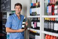 Man holding bottle of alcohol at supermarket portrait mid adult Stock Image
