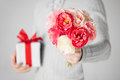 Man holding bouquet of flowers and gift box Royalty Free Stock Images
