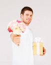 Man holding bouquet of flowers and gift box handsome Royalty Free Stock Image