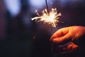 Man holding bright festive christmas sparkler in hand tinted ph photo Royalty Free Stock Photos