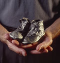 Man holding bronzed baby shoes Royalty Free Stock Image
