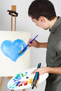 Man holding brushes and palette, painting heart Stock Photography