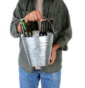 Man holding a bucket of beer closeup in front his body is wearing jeans and shirt with sleeves rolled up vertical Stock Image