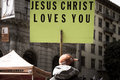Man holding cardboard sign in the street of san francisco with message jesus christ loves you Royalty Free Stock Images