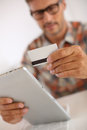Man holding credit card for shopping online trendy guy doing with tablet Stock Photography
