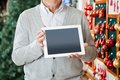 Man holding digital tablet at christmas store midsection of senior Stock Photography