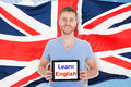 Man holding digital tablet with learn english text young in front of british flag Stock Photo