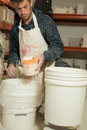 Man holding dipper full of powder plaster alongside two buckets a in splattered clothing a huge white plastic Royalty Free Stock Photo