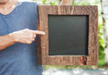 Man holding empty blackboard with wooden frame. Template Mock up Royalty Free Stock Photo