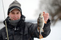 A man holding a fish caught in the winter Royalty Free Stock Photos