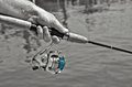 Man holding a fishing pole rod with aqua line in selective color Royalty Free Stock Images
