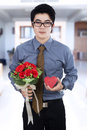 A man holding gift box and flowers businessman at home Stock Photography