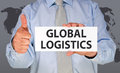 Man holding global logistics sign giving thumbs up caucasian wearing light blue shirt and gray tie that says and a world map in Royalty Free Stock Photography