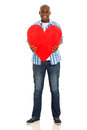 Man holding heart smiling young african shape on white background Stock Photography