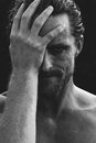 Man holding his head in remorse or regret monochrome greyscale portrait of a hansome bearded with a rueful smile Stock Images