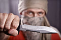 Man holding knife masked a on a black background focus forward Stock Images