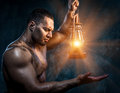 Man holding oil lamp muscular Stock Image