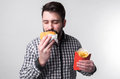 Man holding a piece of amburger and french fries . student eats fast food. not helpful food. very hungry guy Royalty Free Stock Photo