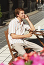 Man holding postcard at outdoor cafe happy young a the Royalty Free Stock Photography