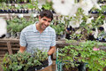 Man holding rack of potted plants Stock Photos