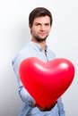 Man holding a red heart balloon brunette wearing blue shirt and Royalty Free Stock Photo