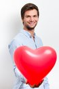 Man holding a red heart balloon brunette wearing blue shirt and Stock Photos