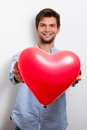 Man holding a red heart balloon brunette wearing blue shirt and Royalty Free Stock Images