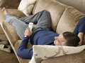 Man holding remote control while lying on sofa middle aged at home Stock Photos