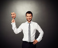 Man holding sad mask smiley businessman over dark background Royalty Free Stock Image