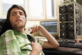 Man holding telephone receiver at computer desk young looking away Royalty Free Stock Photo