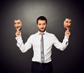 Man holding two masks with different mood serious businessman Stock Image
