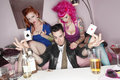 Man holding two playing cards with erotic females sitting besides him Royalty Free Stock Photo