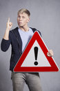 Man holding warning sign with exclamation mark. Royalty Free Stock Images