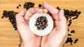 Man is holding white ceramic cup full of coffee beans Royalty Free Stock Photo