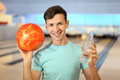 Man holds ball and bottle in bowling club Royalty Free Stock Photography